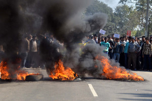 Activists of the Assam Tea Tribes Student Association (ATTSA) block the NH-52 road with burning tyres during a protest against the attacks on villagers by militants from the outlawed National Democratic Front of Bodoland (NDFB) in four locations, at Baghmari in the Sonitpur district of northeastern Assam state on December 24, 2014. © AFP 2015/ STRDEL