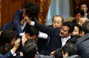 Japanese ruling and opposition lawmakers scuffle at the Upper House's ad hoc committee session for the controversial security bills at the National Diet in Tokyo on Thursday. Photographer: Yoshikazu Tsuno/AFP/Getty Images