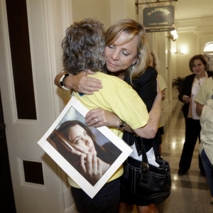 Debbie Ziegler holds a photo of her daughter, Brittany Maynard, as she receives congratulations from Ellen Pontac, after a right-to die measure was approved by the state Assembly, Wednesday, Sept. 9, 2015, in Sacramento, Calif. Rich Pedroncelli/AP