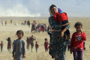 Image: RODI SAID / REUTERS. Displaced people from the minority Yazidi sect, fleeing violence from forces loyal to the Islamic State in Sinjar town, walk towards the Syrian border, August, 2014.