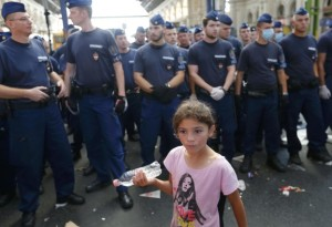 A girl walks past a line of Hungarian police at the main Eastern Railway station in Budapest