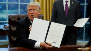 2017: U.S. President Donald Trump holds up the executive order on withdrawal from the Trans Pacific Partnership after signing it as White House Chief of Staff Reince Priebus stands at his side in the Oval Office of the White House in Washington January 23, 2017.   REUTERS/Kevin Lamarque      TPX IMAGES OF THE DAY - RTSWZWJ